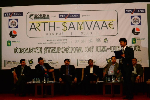 Panel discussion at Arth-Samvaad 2013 being conducted by Abhinandan Ghosh(standing), student at IIM Udaipur. Panelists include (seated from left to right)  Deepak Doegar, CFO, GE Energy India; Mr. Manish Vora, President & Regional Head – Gujarat, Corporate & Institutional & Infra Banking ; Mr. Nitin Parekh, CFO, Cadilla Healthcare, Mr. Makarand Padalkar, CFO, Oracle Financial Services; Mr. Mahesh Taliyani, Group Financial Controller, Shapoorji Pallonji Group, Prof. Ramesh Bhatt, Former Proff, IIMA and Exec. Chairman W One Management Systems